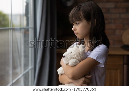 Close up lonely little girl hugging toy, looking out window, standing at home alone, upset unhappy child waiting for parents, thinking about problems, bad relationship in family, psychological trauma