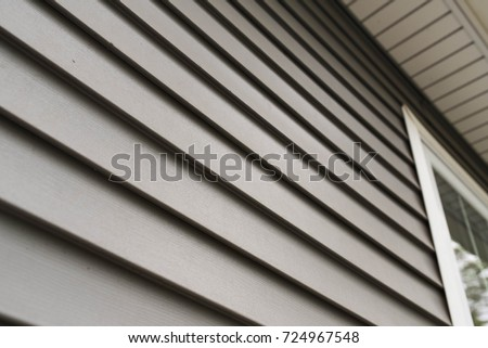 Close up look at vinyl siding on a new home. - Shutterstock ID 724967548