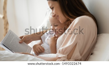 Close up loving caress mother lying with daughter in bed cuddles sweet child reading interesting storybook, preschool smiling kid girl enjoy fairytale before go to sleep good pastime and hobby concept Stock photo ©