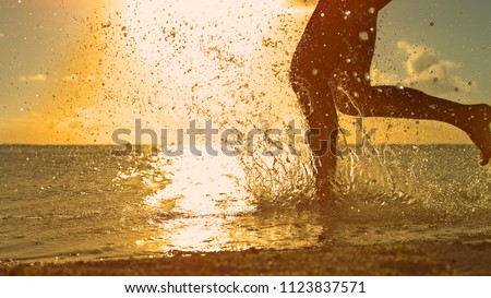 CLOSE UP, LOW ANGLE, SILHOUETTE: Playful girl on holiday runs in the refreshing ocean at sunrise. Unrecognizable young woman goes for a run on the picturesque exotic beach on a sunny summer evening.