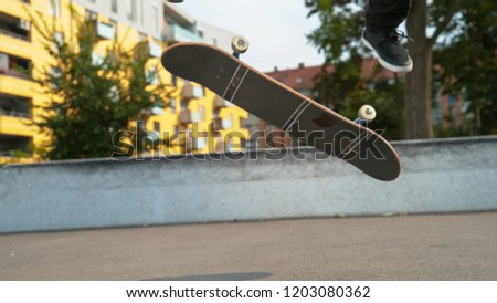 CLOSE UP, LOW ANGLE: Unknown young male skateboarder does a varial kickflip in the empty concrete skate park. Cinematic shot of a skater dude with black pants sticking a trick with his skateboard.