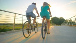 CLOSE UP, LOW ANGLE: Unrecognizable young tourist couple riding their bikes across a highway overpass at sunset. Blonde girl in heels and her boyfriend pedal their bicycles across a modern bridge.