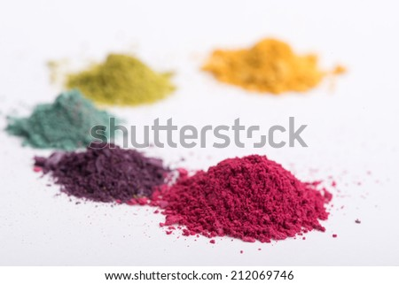 Close-up low angle view of  heaps crashed in small pieces eye shadow in pink, blue, yellow, green and purple colours isolated on white background