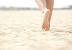 Close up low angle woman barefoot walking on beach