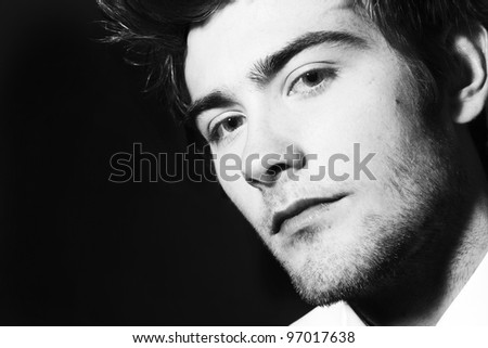 close up low key image of a young man looking at the camera
