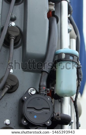 Close up low pressure fuel pump, fuel filter, high voltage wires of boat transom four stroke 4 cylinder fuel injection outboard motor, outboards repair, fuel system maintenance service #1465393943
