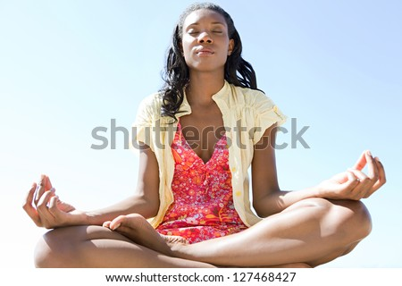 Close up low view of a healthy and attractive african american woman in a yoga position meditating against a bright blue sky on a sunny day.