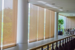 Close up luxury Long blind, curtain, protected sunlight with large glass wall and green tree background.