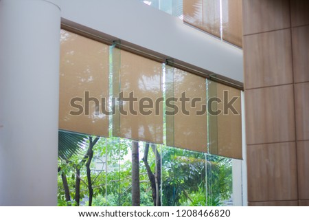 Close up luxury Long blind, curtain, roller, shade, shutter protected sunlight with large glass wall and blur green tree background. #1208466820
