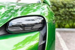 Close-up luxury shiny green sportscar supercar vehicle matrix LED system headlight lamp detail parked on city street outdoors. Electric car front bumper part