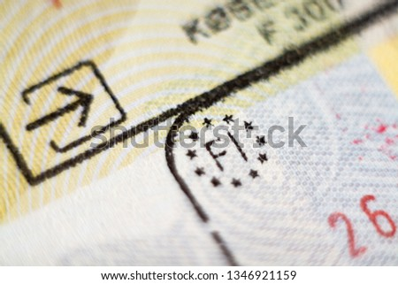 Close-up macro detail of European Union border control customs admission stamp with enter symbol in focus and Finland country marking sign #1346921159