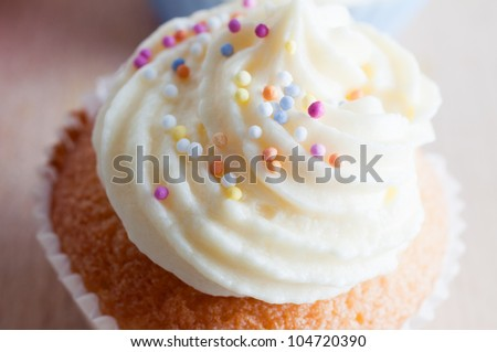 Close up ((macro) of a freshly baked cupcake decorated with a swirl of  buttercream icing and colourful  sprinkles.