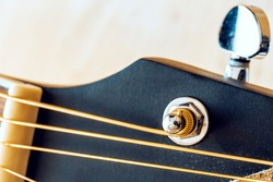 Close-up macro of a guitar string on a tuning peg on the fretboard