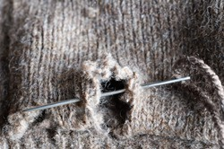 Close up (macro) of a threaded needle, darning a hole in an old frayed woolen garment.  To suggest needlework, recycling or frugality during recession.