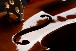 Close up macro of F hole on brown wooden fiddle or violin, classic musical instrument, over black background, selective focus