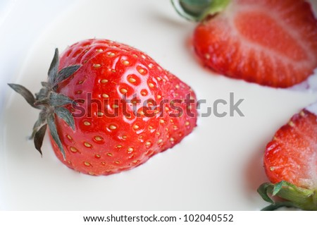 Close up (macro) of fresh strawberries sunk into rich double cream.