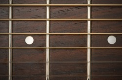 close-up macro of guitar strings and fret board