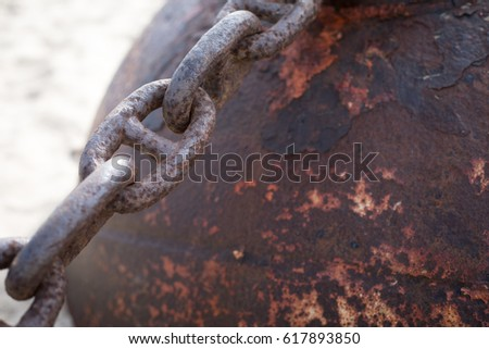 Close up macro of weathered and aged industrial rusted iron ball anchor buried in beach sand with chain links #617893850