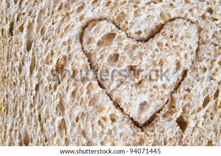 Close up (macro) of wholemeal bread with a heart shape cut into it, to illustrate love or a healthy heart diet.