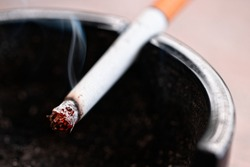 close up, macro shot of a burning cigarette in an ashtray