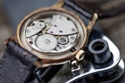 Close up macro shot of a vintage/retro AVIA mens mechanical wrist watch, showing its workings. With a assortment of watch making, fixing instruments and tools around the watch. Lovely well lit scene.