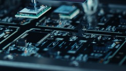 Close-up Macro Shot of Electronic Factory Machine at Work: Printed Circuit Board (PCB) Being Assembled with Automated Robotic Arm, Surface Mounted Technology (SMT) Connecting Microchips to Motherboard