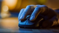 Close-up Macro Shot: Person's Hand Using Wireless Computer Mouse, Scrolls through Apps and Websites with a Wheel and Clicks on Buttons. In the Background Evening Light