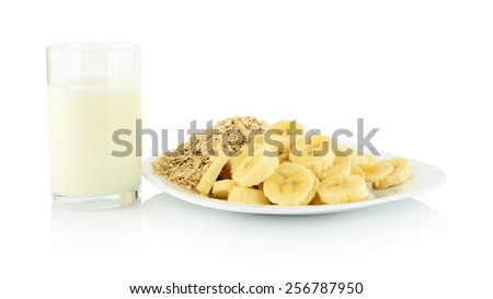 Close-up macro studio shot slices banana on plate with glass of milk on white background