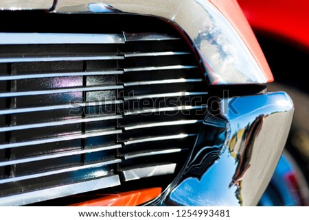 Close up macro view of the chrome grill and bumper of an vintage retro muscle automobile, parked in a mountain tourist area during a classic american car owners meeting.