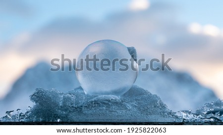 close up makro shot of beautiful frozen bubbles bedded on a pile of white snow and blue ice with a delicate structure of ice flowers back-lit by the rising sun with mountains in the background Stock foto ©
