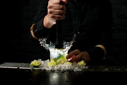 Close-up. Male barman holds black madler in his hand and energetically squeeze slices of citrus to cocktail. Pieces of ice and lime at the bar.