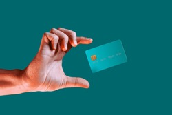 Close up male hand and levitating template mockup bank credit card with online service isolated on green background