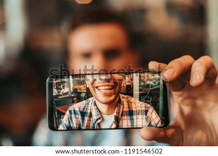 Close up male hand demonstrating screen of phone with picture of dude mouth with teeth. Glad guy having fun with gadget concept