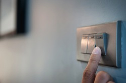 Close up male hand or fingers turn on or off on grey light switch with dark blue wall in the night time at home. Power, Energy, Safety, Saving Electrical. Copy space.