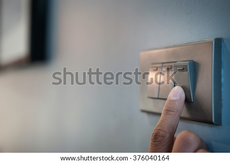 Close up male hand or fingers turn on or off on grey light switch with dark blue wall in the night time at home. Power, Energy, Safety, Saving Electrical. Copy space.  Foto d'archivio ©