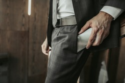 Close up male hand putting contemporary phone in pocket of trousers. He standing indoor