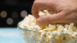 Close up male hand taking popcorn from glass bowl