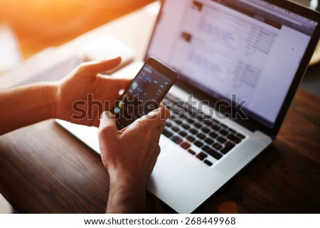 Close up male hands holding big smart phone while connecting to wireless, businessman using technology sitting at modern loft wooden desk, people and modern devices everywhere, flare sun light