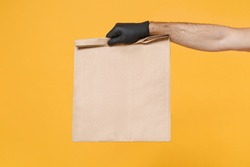 Close up male hold in hand glove brown clear empty blank craft paper bag for takeaway isolated on yellow background. Packaging template mockup. Delivery service concept. Copy space Advertising area