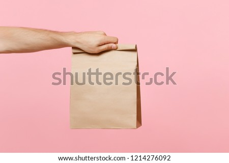 Close up male holding in hand brown clear empty blank craft paper bag for takeaway isolated on pastel pink background. Packaging template mock up. Delivery service concept Copy space advertising area