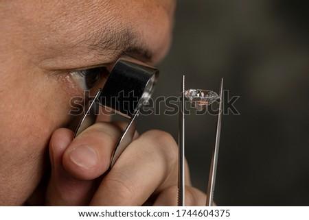 Close up male jeweller. Jeweller looking diamond though loupe. Cut and polished diamond. Big size diamond. Brilliant, magnifier, tweezers. Diamond expert.