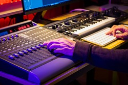 close up male sound engineer hand mixing music on digital audio mixing board in sound studio. music production concept