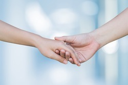 close up man and woman hand touching holding together on blurred background for love and healing concept