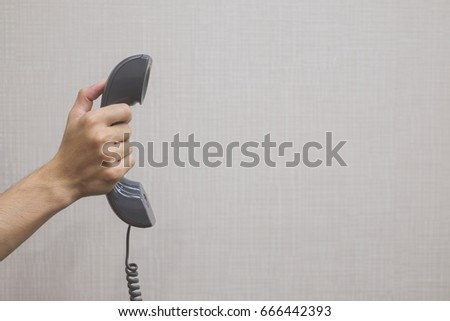 close up man hand hold handset telephone on background concept.