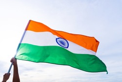 Close up man hand holding India flag on the blue sky background. Indian Independence Day, 15 August.