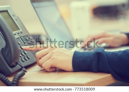 close up man hand point to press button number on telephone office desk.hotline employee concept