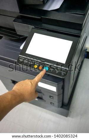 Close-up man Hand press button on panel of printer, printer scanner laser office copy machine supplies start concept.