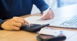 close up man hand writing on notebook and calculating on calculator about debt bills monthly at the table in home office and managing expense payroll,money risk financial concept