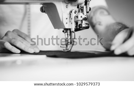 Close-up man hands sewing fabric on sewing machine