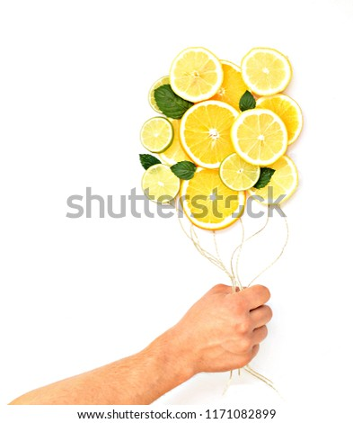 Close-up - man holds cords in hand where slices of lemons, limes and oranges are hanging - concept with citrus balloons hovering in front of a monochrome background with space for text #1171082899